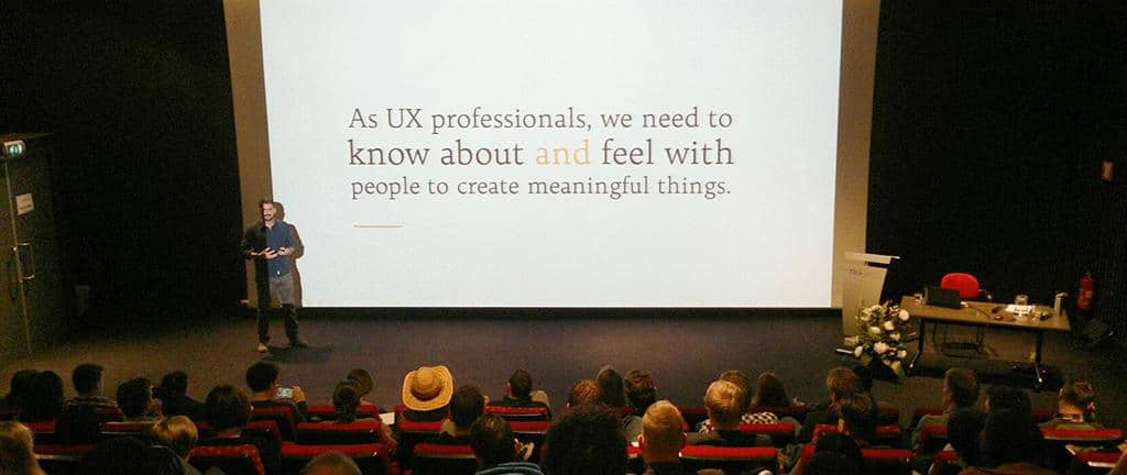 """Photo of Brian Pagán on stage at UXcampNL in 2014. The slide reads """"As UX professionals, we need to know about and feel with people to create meaningful things."""""""